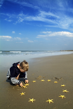 Criança brinca com estrela-do-mar na praia