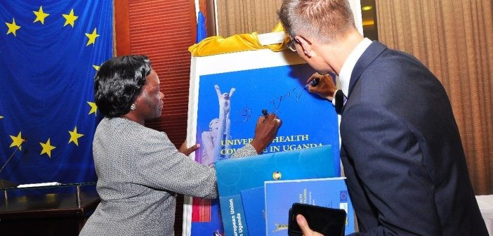Minister Sarah Opendi and Mr. Thomas Tiedemann autograph a large format book cover print-out at the ceremony