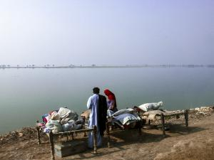 A Pakistani family sets up camp by flooded lands