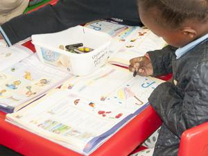 A school child in Tembisa using one of the text books