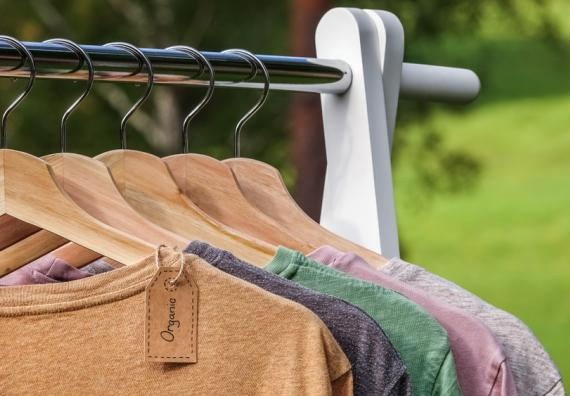 Colourful t-shirts hanged on a rack showing the organic tag