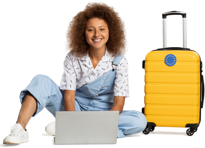 Enthusiastic young woman sitting on the floor next to a suitcase and typing on a laptop