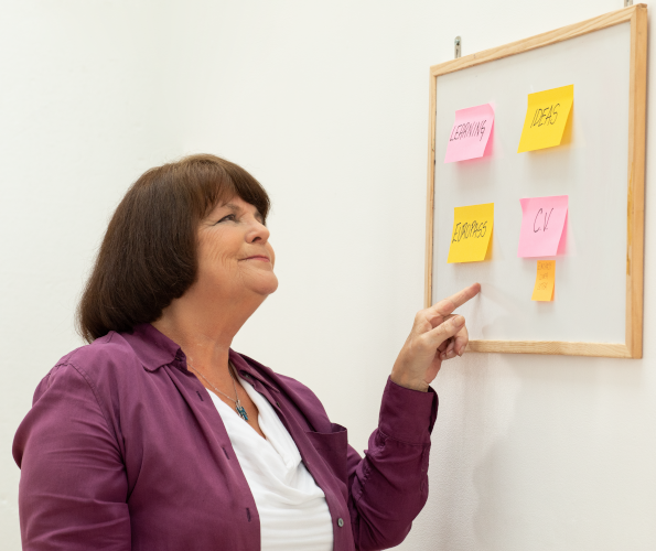 Woman pointing at a white board with sticky notes about learning and skills