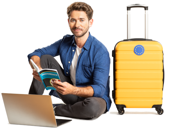 Man sitting next to a laptop and a suitcase, and reading a book