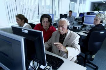 Young and elderly people working in an office © EU