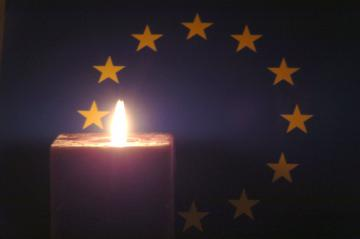 A candle lit up in front of the EU emblem © EU