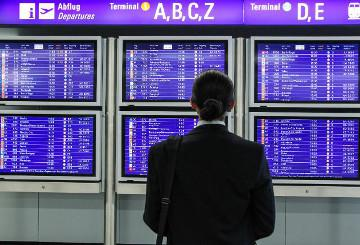 A woman checking the flights schedule in an airport © EU
