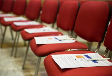 Chairs lined up with a conference programme placed on them © EU