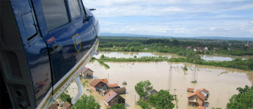 A civil protection helicopter flying over a flooded area © EU