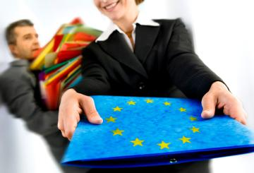 A woman holding a file with the EU emblem © EU