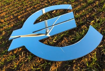 A mirror in the shape of the euro symbol, mirroring a windmill in a field © EU