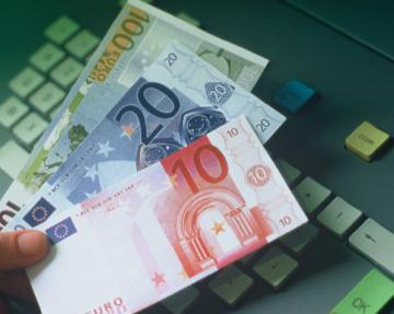 A person holding euro banknotes above a keyboard © EU