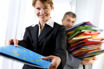 A woman holding a folder with the EU emblem while a man holds a pile of other folders in the background © EU