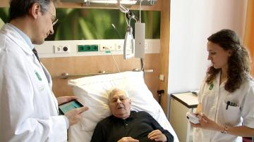 Man lying in a hospital bed talking to healthcare professionals © EU