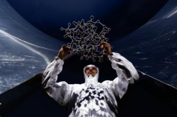 A scientist holding a structure made of atoms © EU