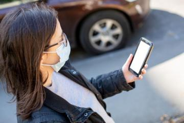 A woman wearing a mask and reading on her smartphone on the go © EU