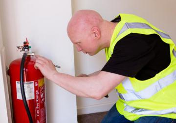 A man wearing a safety vest and checking a fire extinguisher © EU