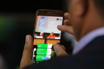 A person following an online event on their smartphone © EU