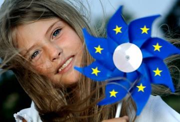 A girl holding a windmill in the colours of the EU emblem © EU