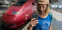 Woman standing next to train using Wi-Fi network on mobile phone © EU