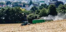 Combine harvester and tractor with a trailer in wheat field © EU
