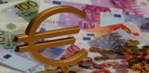 Euro symbol with euro coins and bills in the background © EU