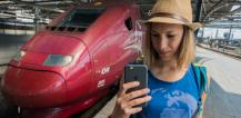 Young woman using mobile from next to a train © EU