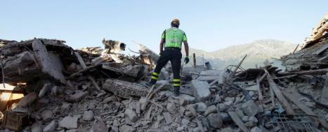 A rescuer and a sniffer dog standing atop rubble, in Amatrice © EU