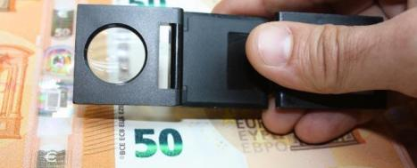 Hand holding magnifying glass over 50 euro notes © EU