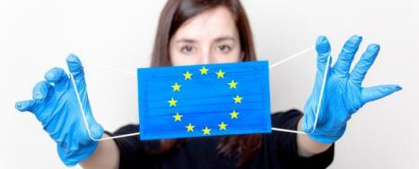 Woman holding face mask with European flag © EU