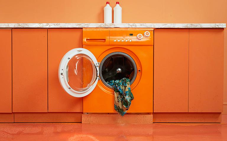 image of an orange dryer with wet clothes coming out