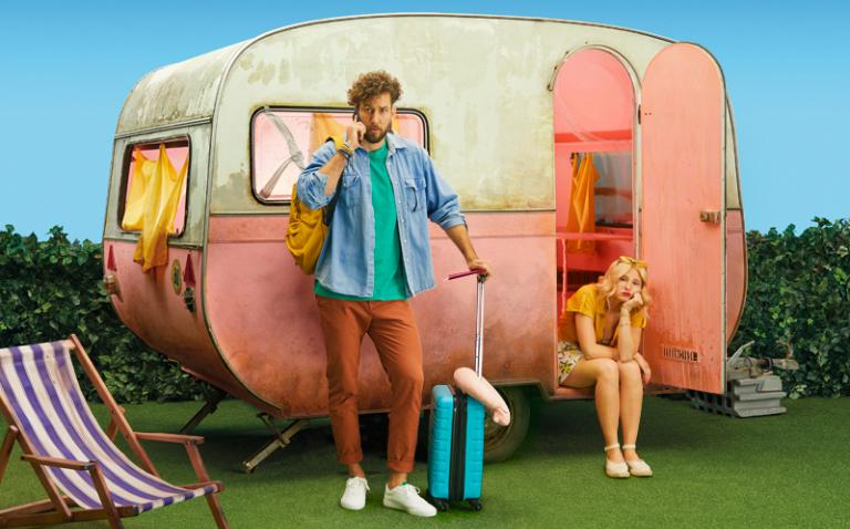 travel package image with couple and dirty caravan
