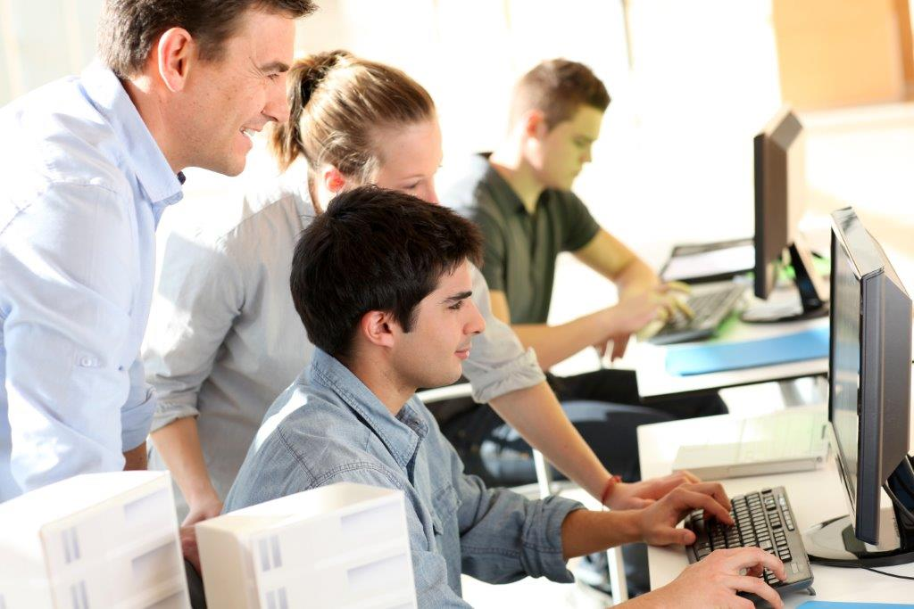 young people with an adult mentor at computers