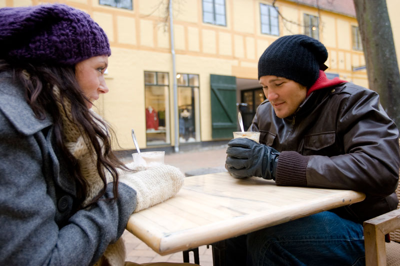 Two young people, dressed warmly, drinking coffee. Source: Colourbox.com