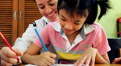 A volunteer teaches a girl how to draw