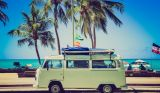Green campervan with palm trees and sea